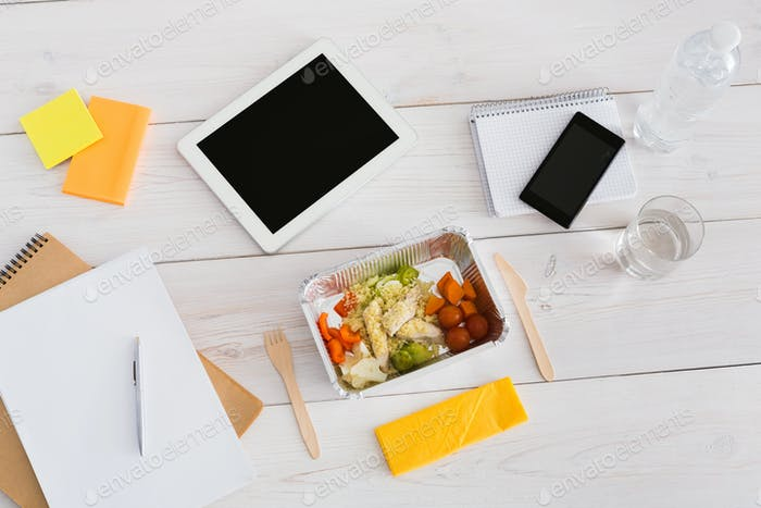Healthy lunch foil box with diet food on office table