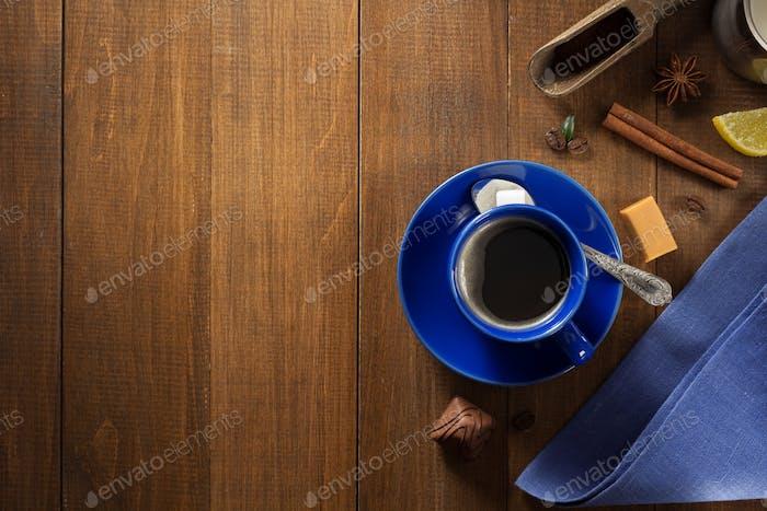 Tasse Kaffee und Bohnen auf Holz