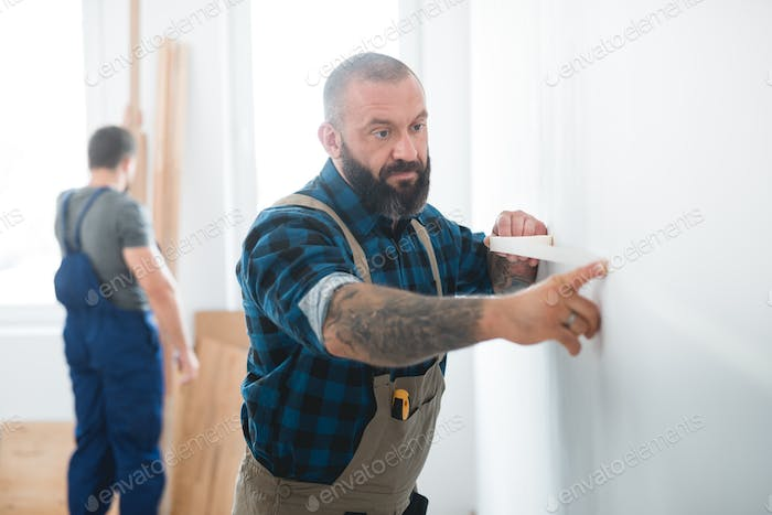 Professional builder puts a tape on an empty wall before painting it