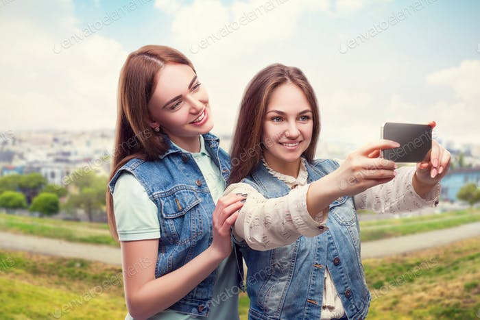 Girlfriends makes selfie, cityscape on background