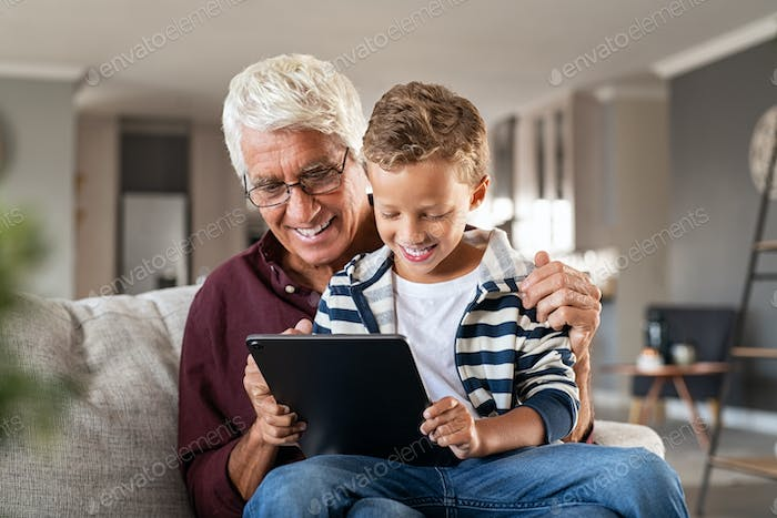 Grandfather and grandchild using digital tablet at home