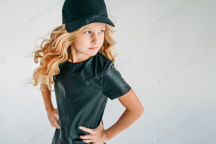 Curly hair tween girl in black leather dress and baseball cap on white background