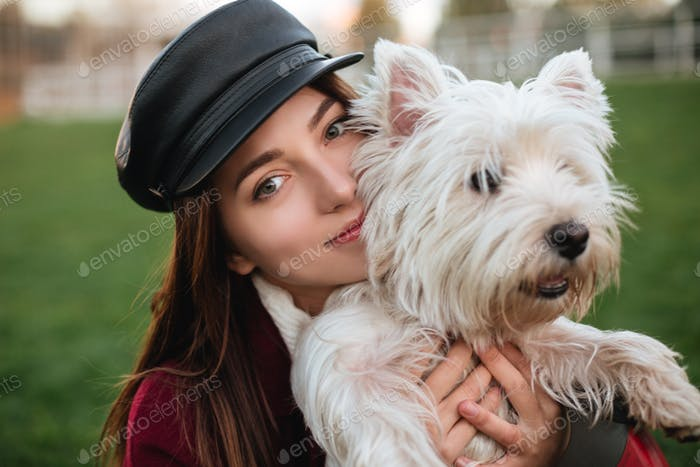 Beautiful lady in cap and coat dreamily looking in camera while hugging her small cute dog in park