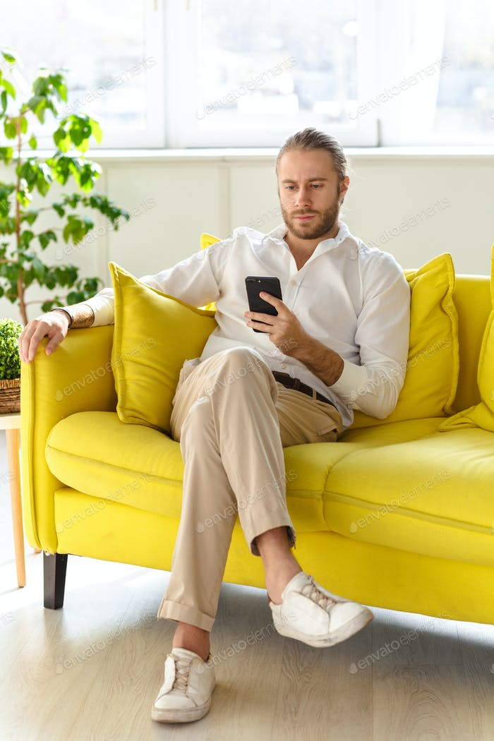 Photo of businessman holding cellphone while sitting on sofa in apartment