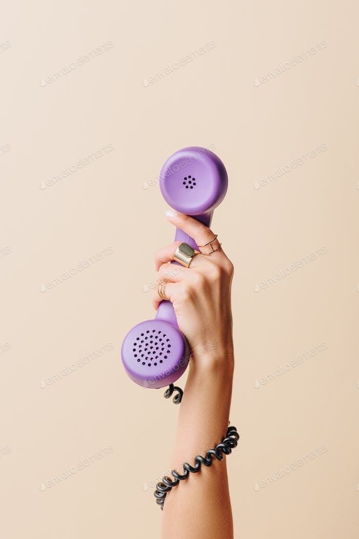 partial view of woman holding purple phone tube on beige