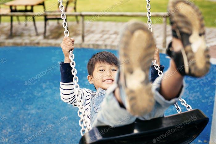 Boy (4-5) on swing