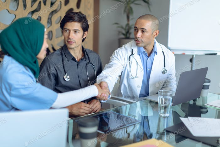Diverse medical team with stethoscopes around the neck shaking hands at table in the hospital
