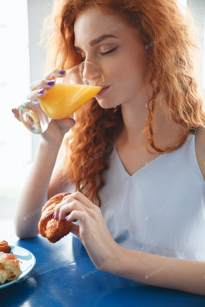 Redhead lady sitting at the table indoors drinking juice