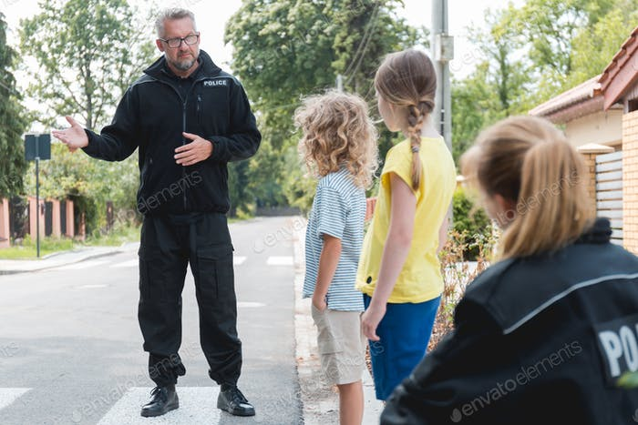 Handsome policeman explains to children the rules of safe movement on the street
