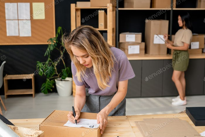 Young serious female manager of online shop writing down address of receiver