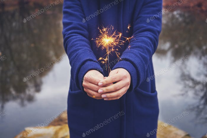 Woman holding sparkler in forest, winter day