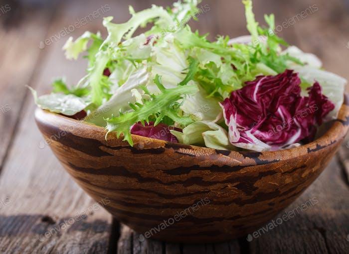 Grüner Salat in einer Holzschüssel.Capriccio.