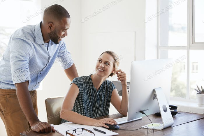 Man stands talking to woman smiling at her desk in an office