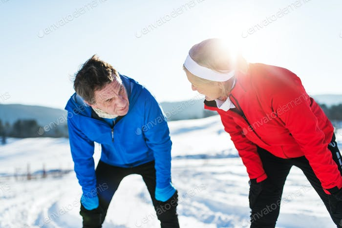 Senior couple runners standing in winter nature, resting.