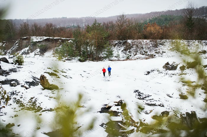 A senior couple jogging in snowy winter nature.