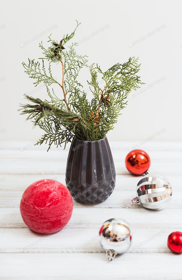 Christmas composition with spruce branches, candles, a vase