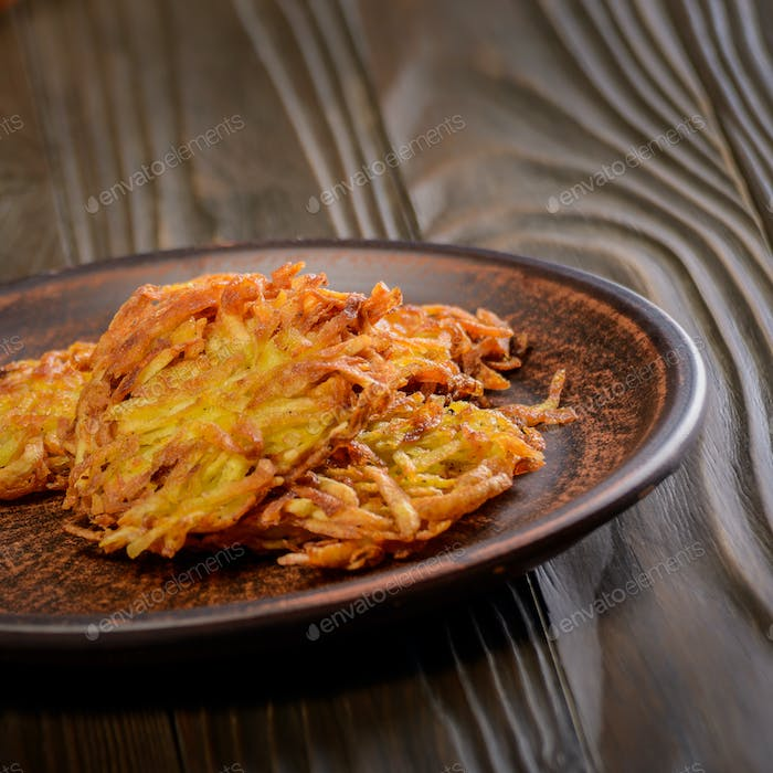 Fresh homemade tasty potato pancakes in clay dish on rustic wood