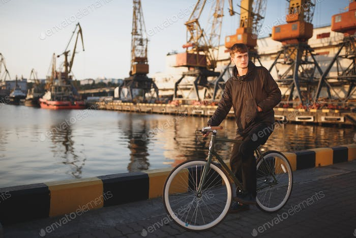 Young man with brown hair standing with bicycle and thoughtfully looking aside