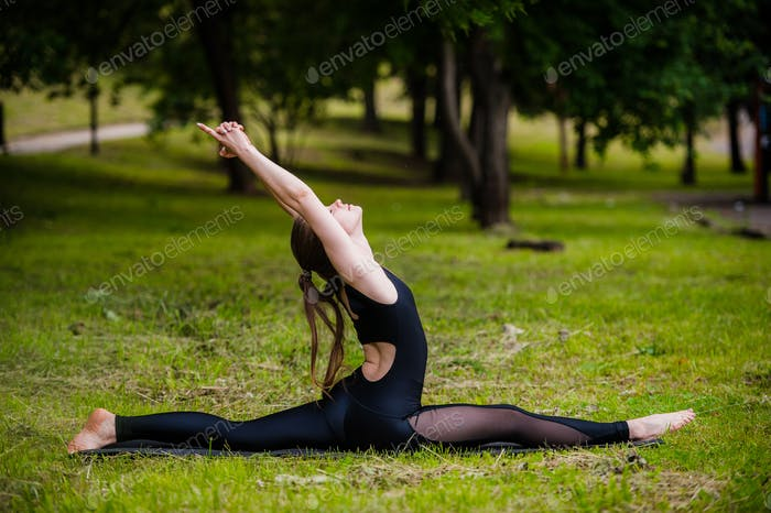 Beautiful young woman doing relaxing and stretching exercises in the park.