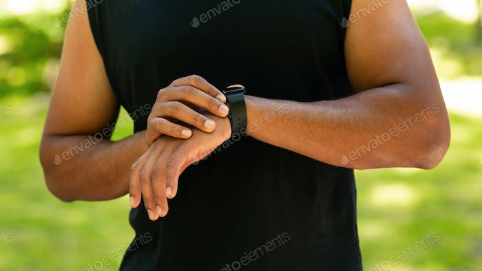Cropped view of black guy checking his smartwatch or fitness tracker while working out outdoors
