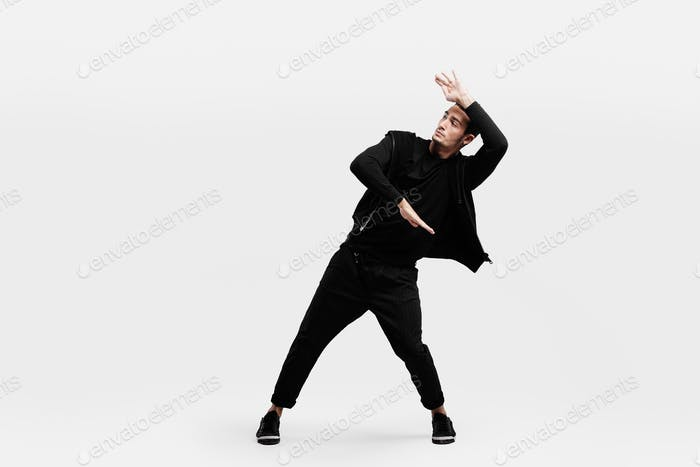Dark-haired stylish man dressed in a stylish black clothes is dancing street dance. He makes