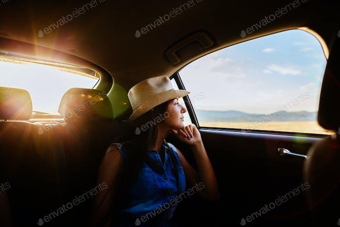 Frau reisen und träumen mit dem Auto mit Sonnenlicht und malerische Aussicht