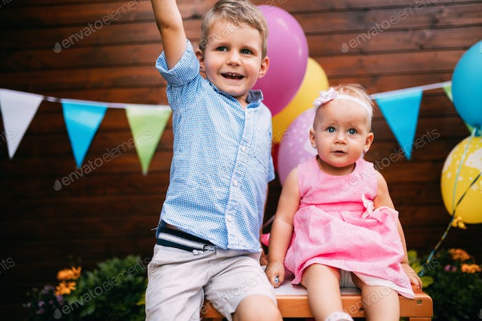 Happy young boy and little girl at birthday party