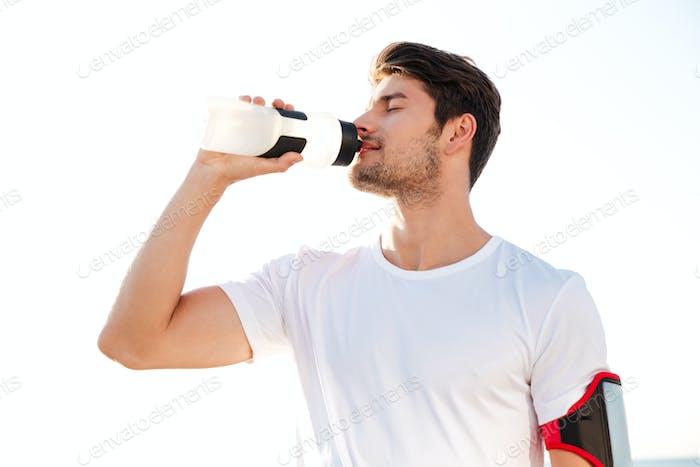Durstige Sportler trinken Wasser nach dem Training