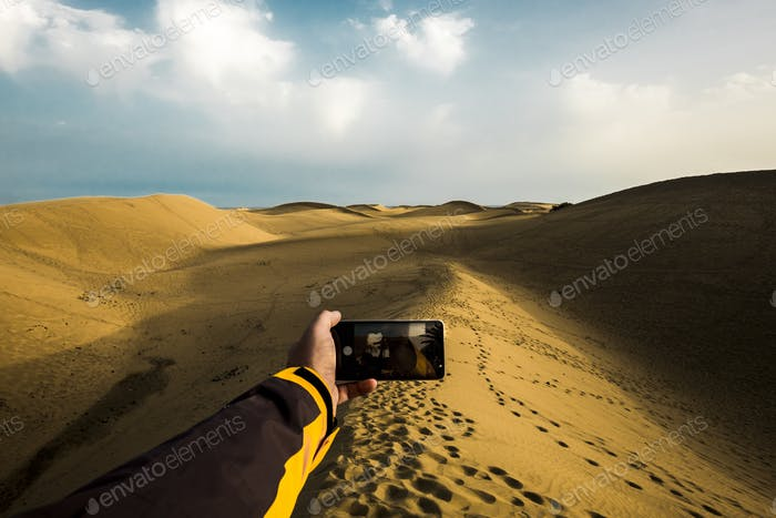 Kaukasische Hand mit moderner Technologie, Telefon, das Foto macht, wenn sandgelbe Wüste