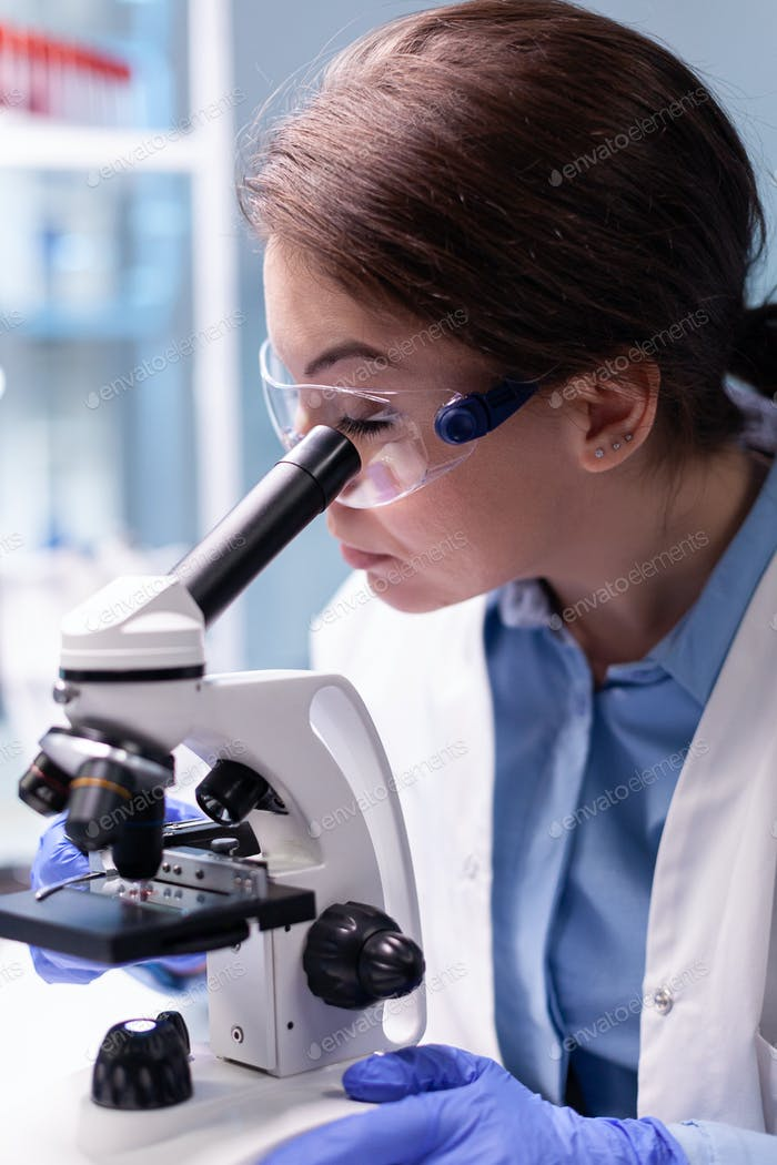 Medical scientist analyzing a test with microscope for pharmaceutical expertise