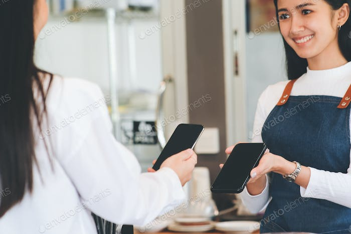 Satisfied customer paying through mobile phone using contactless technology.