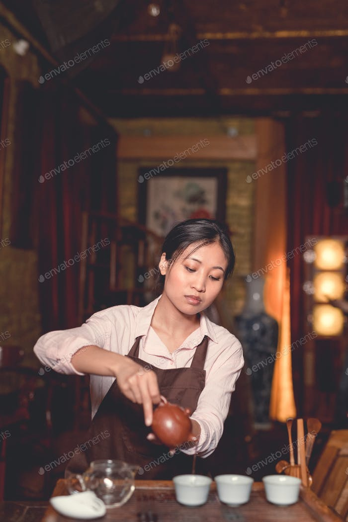 Young asian girl pouring tea