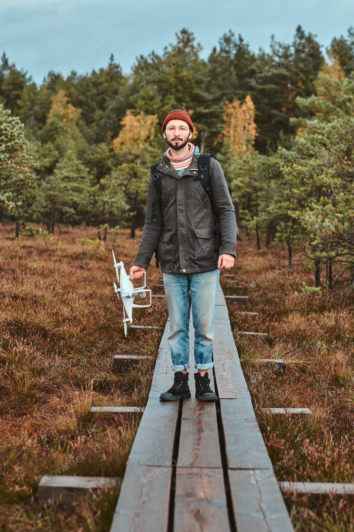 Young man is walking in forestal park with his drone