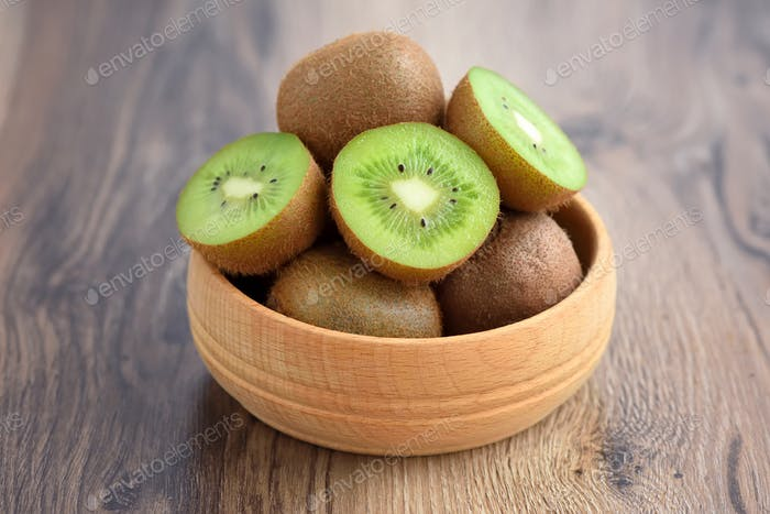 Kiwi fruit in a bowl on wooden background