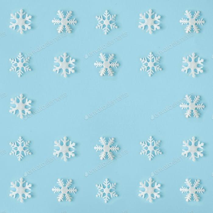 Kreative Schneeflocken Muster mit leuchtend blauen Hintergrund. Minimaler Winterflachlag Weihnachtskonzept.
