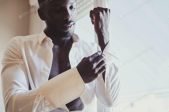 Элегантный человек одевает запонки