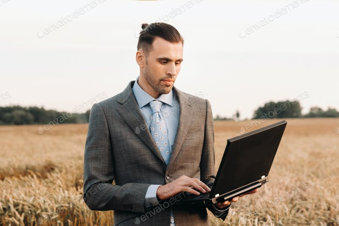 Portrait of a businessman in a suit holding a laptop in a field of wheat against the background of a