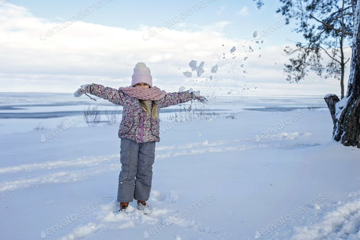 Girl have fun on the frozen lake in snowy winter day, seasonal outdoor activities, lifestyle