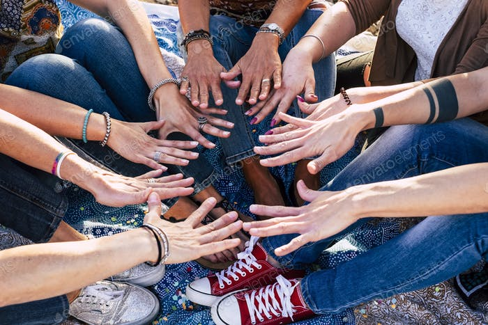 Close up top view of people putting their hands together. Friends unity and teamwork
