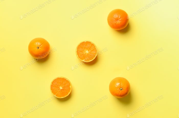 Fruit pattern of fresh orange slices on yellow background. Top view. Copy Space. Pop art design