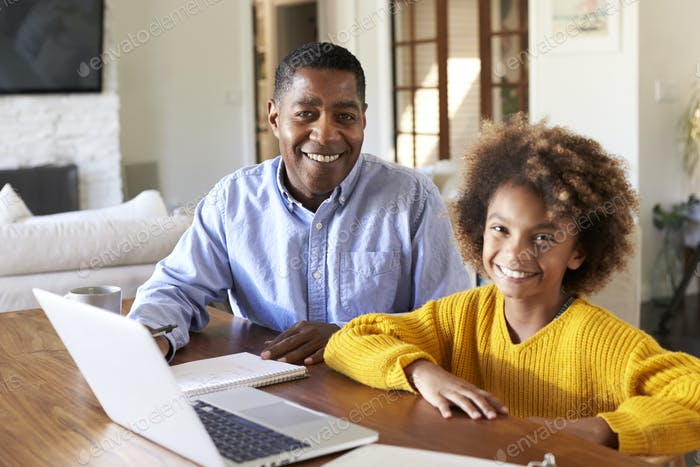 Pre-teen black girl and her male home tutor sitting at a table in the dining room smiling to camera