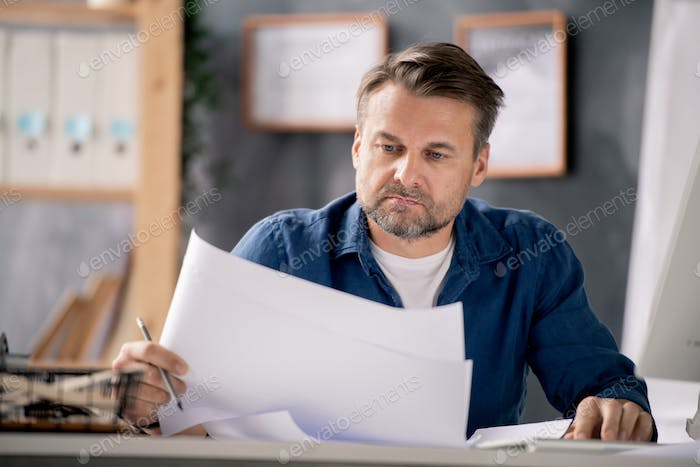 Mature serious architect in casualwear checking sketches by desk in office