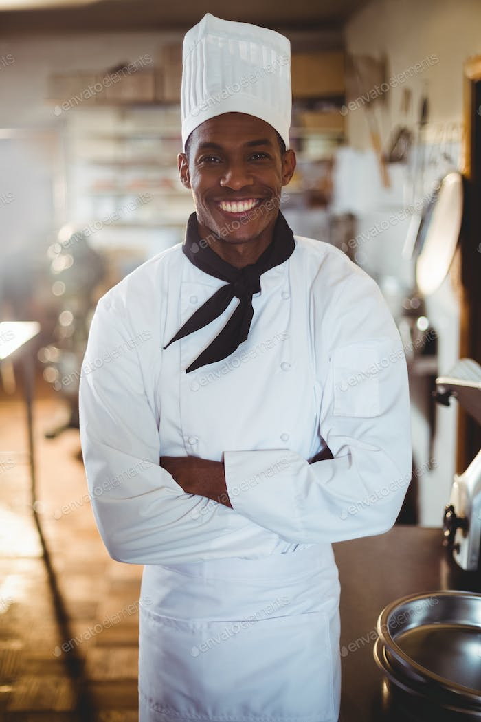 Portrait of smiling chef standing with arms crossed