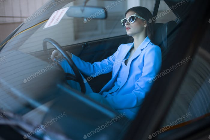 Fashion lady driving a car in a blue suit. Stylish girl sitting in the car holding steering wheel