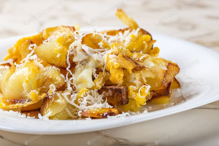 Fried potatoes with scrambled eggs and parmesan cheese