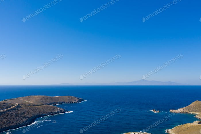 Calm clear water, blue sky background. Aerial drone view