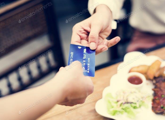 Frau, die Mittagessen mit Kreditkarte im Restaurant