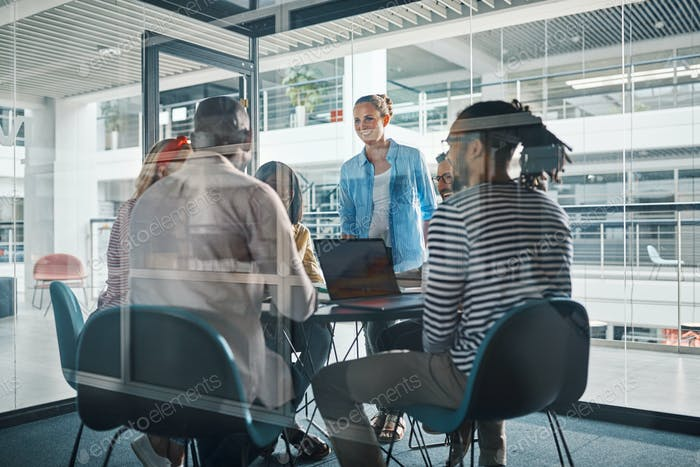 Diverse businesspeople meeting together inside a glass walled boardroom