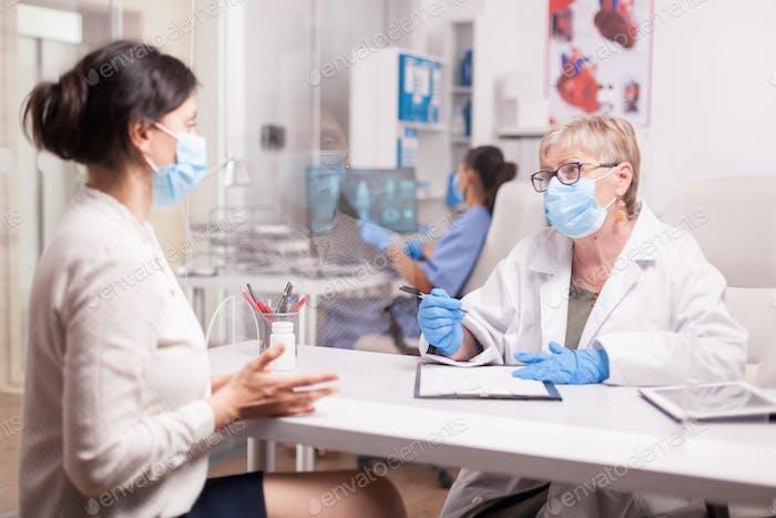 Reifer Arzt mit Gesichtsmaske gegen Coronavirus