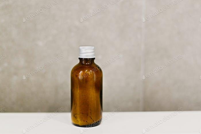 Ayurveda ubtan powder in glass bottle on white sink